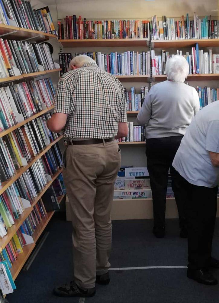 elderly people in library hepling each other